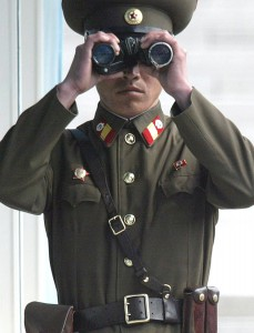 PANMUNJOM, SOUTH KOREA - MARCH 26: A North Korean soldier looks through binoculars to survey across the Demilitarized Zone (DMZ) dividing the two Koreas March 26 2003 at Panmunjom, South Korea. North Korea pulled out of regular military meetings with U.S.-led United Nations Command March 26, 2003. North Korea accuses the U.S. of preparing for an invasion by holding military exercises with the South Korean army. (Photo by Chung Sung-Jun/Getty Images)